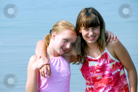 Two preteen girls stock photo, Portrait of two preteen girls standing in water by Elena Elisseeva