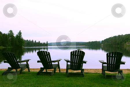 Four Lake chairs stock photo, Four wooden adirondack chairs on a shore of a beautiful lake at dusk by Elena Elisseeva