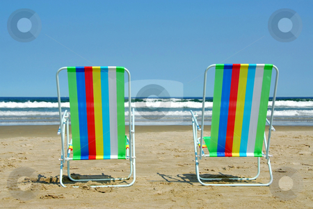 Vacation paradise stock photo, Two colorful beach chairs on the ocean shore by Elena Elisseeva