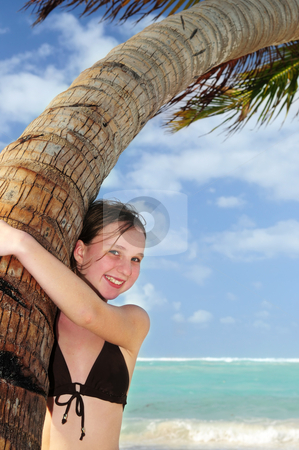 Young girl with seashell stock photo, Happy young girl higging a palm tree on tropical beach by Elena Elisseeva