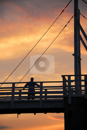 Man watching sunset stock photo, Man watching sunset on a footbridge in Perkins Cove, Maine by Elena Elisseeva