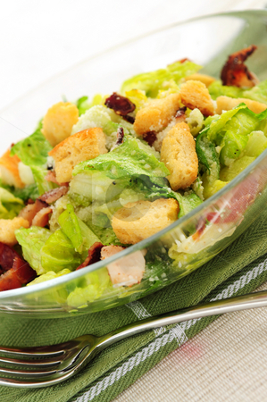 Caesar salad stock photo, Caesar salad with croutons and bacon bits served in a glass bowl by Elena Elisseeva