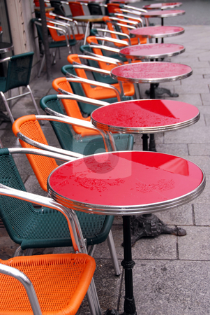Sidewalk cafe stock photo, Bright colorful tables in a sidewalk cafe with rain drops by Elena Elisseeva