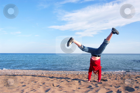 Girl doing cartwheel stock photo, Young girl doing cartwheel on a beach by Elena Elisseeva