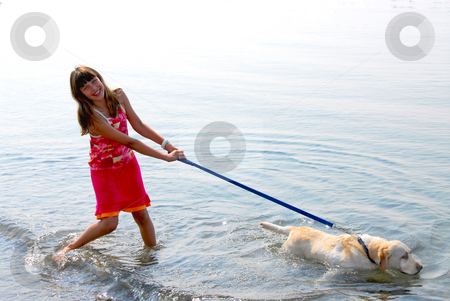 Girl playing dog stock photo, Happy girl playing with her dog in water by Elena Elisseeva
