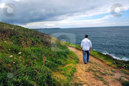 Brittany coast stock photo, A man walking on a hiking trail along the coast of Brittany, France by Elena Elisseeva