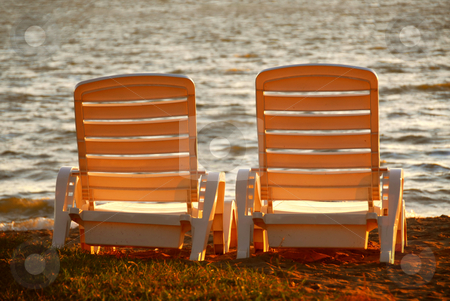 Beach chairs stock photo, Two plastic beach chairs on a shore in late afternoon sunlight by Elena Elisseeva