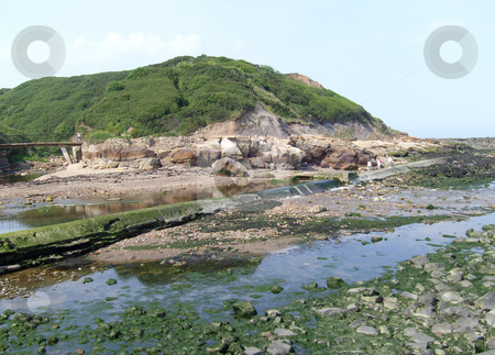 Rock pools by seashore stock photo, River leading to seashore filling rock pools in beach scene. by Martin Crowdy