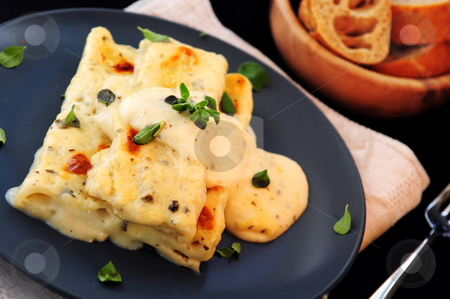Cannelloni pasta stock photo, Cheese cannelloni pasta served on a plate with alfredo sauce by Elena Elisseeva