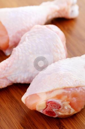 Raw chicken drumsticks stock photo, Raw chicken drumsticks on a wooden cutting board by Elena Elisseeva