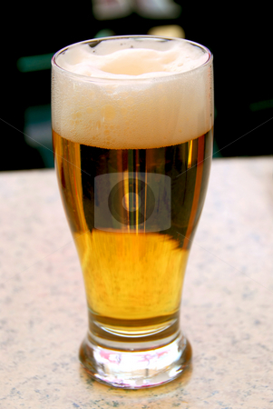 Beer stock photo, Pint of freshly poured beer on a table in outdoor restaurant patio by Elena Elisseeva