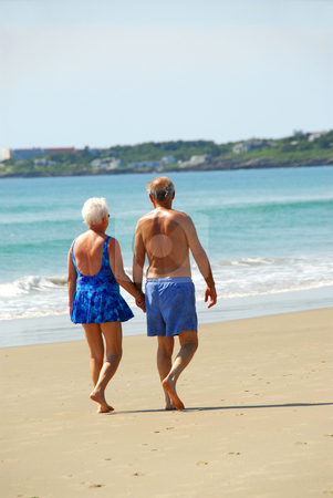 Happy retired couple stock photo, Happy retired couple taking a walk on a beach holding hands by Elena Elisseeva