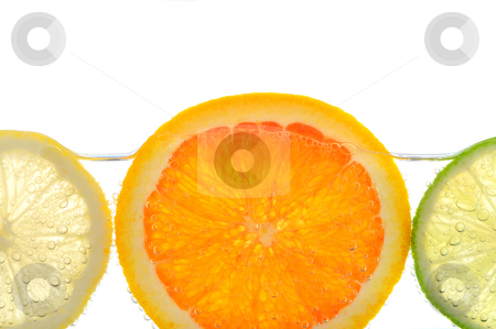 Orange lemon and lime slices in water stock photo, Orange lemon and lime slices in water with air bubbles on white background by Elena Elisseeva
