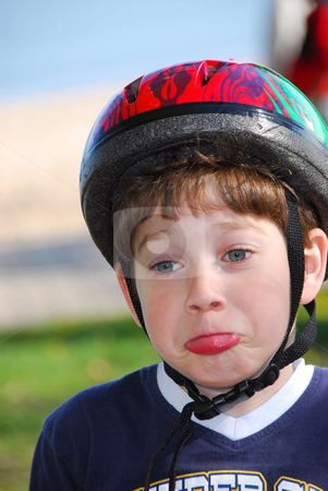 Cute boy portrait stock photo, Portrait of a cute little boy in bicycle helmet making faces by Elena Elisseeva