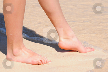 Trying water stock photo, Feet of a young woman touching water on tropical beach by Elena Elisseeva