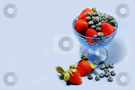 Berries on blue stock photo, Berries in a glass bowl on blue background, space for copy by Elena Elisseeva