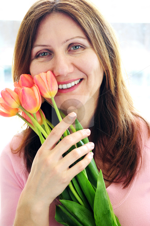 Caucasian woman with flowers stock photo, Smiling mature woman holding bouquet of flowers by Elena Elisseeva