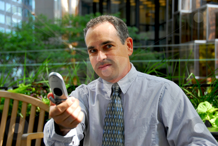Businessman phone stock photo, Portrait of a busy businessman in the city holding a cell phone by Elena Elisseeva