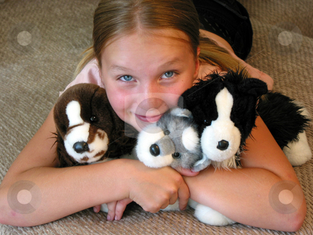 Girl hugging her plush toys stock photo, Happy young girl with her favourite plush toys. by Elena Elisseeva