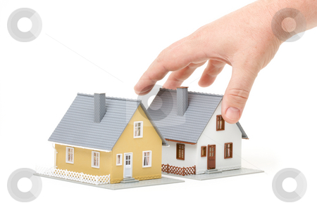 Choosing A Home stock photo, Male hand reaching for house isolated on a white background. by Andy Dean