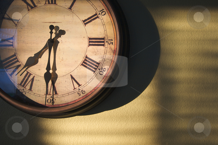 Antique Clock On Wall stock photo, Antique Clock on an olive green wall with dramatic evening light and shadows. by Andy Dean