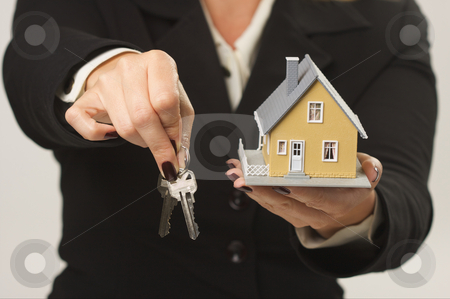 House and Keys in Female Hands stock photo, Female presenting keys and small house. by Andy Dean