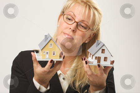 Woman Holding Two Houses stock photo, Female holding two houses contemplating each. by Andy Dean