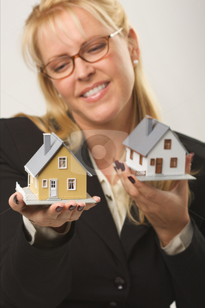 Houses in Female Hands stock photo, Female holding two houses contemplating each. by Andy Dean