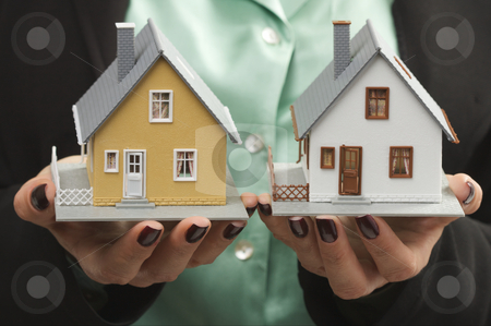 Houses in Female Hands stock photo, Female hands holding two houses. by Andy Dean