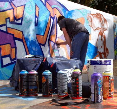 Graffiti artist at work with tools stock photo, A photograph of an unidentifiable graffiti artist spray painting a public wall, with paint and cans in the foreground by Philippa Willitts