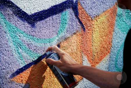 Graffiti in Progress stock photo, A silhouetted man spray painting graffiti onto a wall by Philippa Willitts
