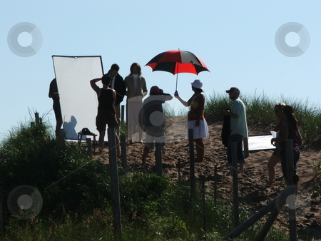 Advertising Photo Shoot stock photo, Sand hills on a Lake Superior beach in Duluth, Minnesota provide the scene for an advertising agency photo shoot complete with models, umbrellas, make-up crew and lighting crew. by Dennis Thomsen
