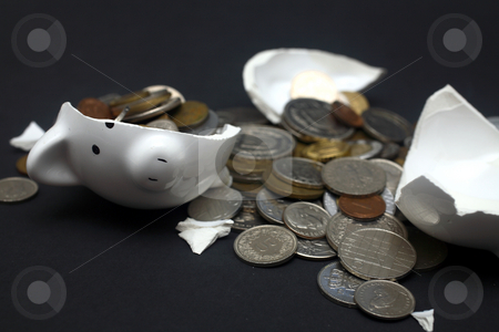 Broken Piggy Bank stock photo, A broken piggy bank isolated on a dark background with loads of coins from around the world. by Daniel Wiedemann