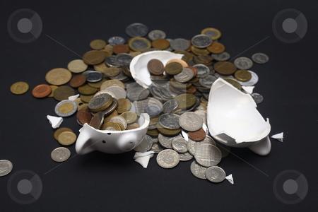 Broken Piggy Bank stock photo, A broken piggy bank isolated on a dark background with loads of coins from around the world. by Daniel Wiedemann