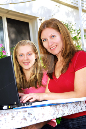 Mother and daughter with computer stock photo, Mother and daughter working on a portable computer at home in the garden by Elena Elisseeva
