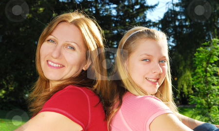 Mother and daughter stock photo, Portrait of smiling mother and daughter in summer park by Elena Elisseeva