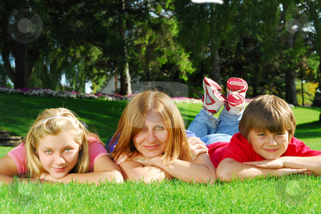 Family relaxing stock photo, Family of happy mother and children relaxing on green grass by Elena Elisseeva