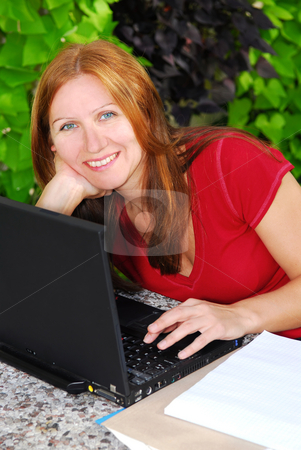 Working at home stock photo, Happy mature woman working on portable computer at home, small business owner by Elena Elisseeva
