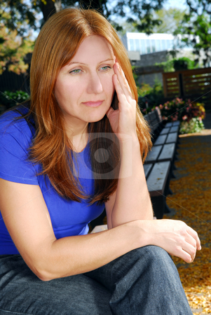 Sad woman stock photo, Mature woman looking sad and stressed sitting on a park bench by Elena Elisseeva