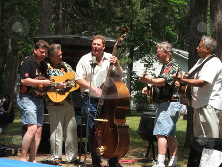Bluegrass in the park stock photo, A bluegrass band performs on a riverside park in north central Minnesota. Small town celebrations, like Sommerfest in Pine River, Minnesota usually mean relaxing, free entertainment, carnival rides and a parade. by Dennis Thomsen