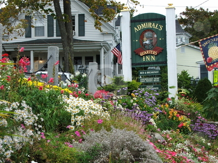 Flower Garden Glory stock photo, A flower garden bordering a narrow street near the harbor in Boothbay Harbor, Maine remains in full bloom in early October.  In the background is  the advertising sign for one of Boothbay's many inns and bed and breakfasts available to tourists visiting this restful fishing village on the Maine coast. by Dennis Thomsen