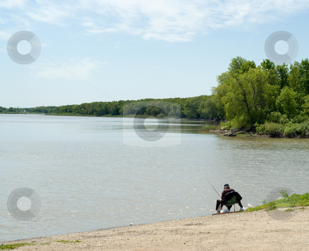 Gone Fishing stock photo, A man sitting in a chair by the river, enjoying a sunny day fishing by Richard Nelson