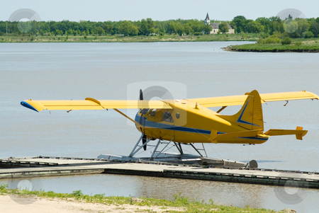 Yellow Seaplane stock photo, A yellow seaplane docked on the river during the day by Richard Nelson