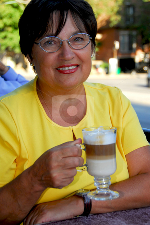Mature woman coffee stock photo, Happy mature woman in outdoor cafe holding a coffee by Elena Elisseeva