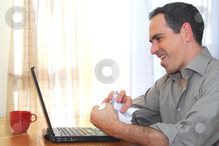 Man with laptop stock photo, Man sitting at his desk with a laptop crumpling papers by Elena Elisseeva