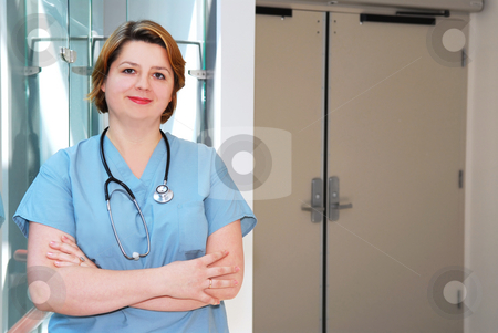 Nurse in a hospital stock photo, Portrait of a smiling nurse in a hospital by Elena Elisseeva