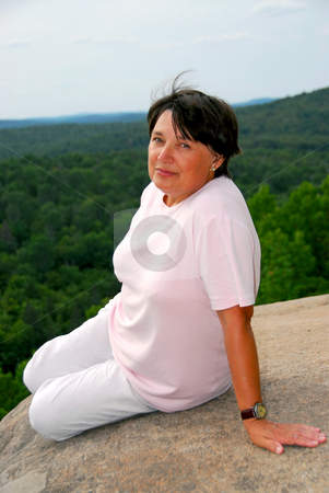 Woman edge cliff stock photo, Mature woman sitting on scenic cliff edge by Elena Elisseeva