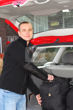 Man car luggage stock photo, Man loading bags in the trunk of his car by Elena Elisseeva