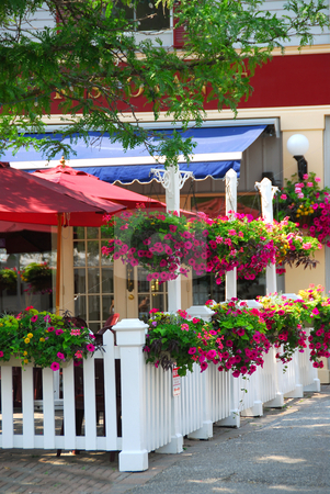 Restaurant patio stock photo, Pretty restaurant patio decorated with purple petunia flower boxes and baskets by Elena Elisseeva