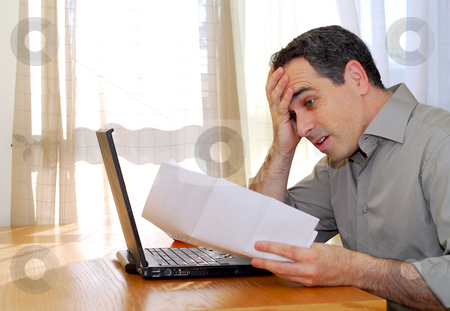 Man with laptop stock photo, Man sitting at a desk looking at bills with horror by Elena Elisseeva